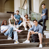Six international students sitting in a relaxed manner in the hallway of a university. They smile towards the camera.